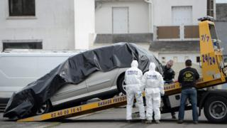 Forensic investigators are at work near the car of Sebastien Troadec after it was found in a parking lot in Saint-Nazaire