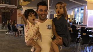 A man in an England shirt holds his two children. Both girls are yelling and gesturing.