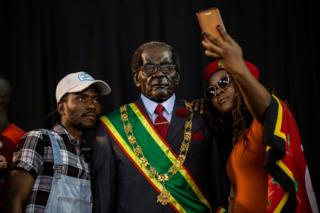 Attendees at the South African political party, the Economic Freedom Fighters (EFF) hosted memorial service held in honour of late Zimbabwean President Robert Mugabe take pictures with a wax model of the Former President in Soweto, Johannesburg on September 12, 2019.