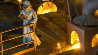 A worker wearing protective clothing agitates molten steel at the Saint-Gobain PAM factory in Pont-A-Mousson, north-eastern France. (April 2016)