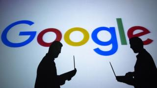 Two men holding laptops in front of a Google sign