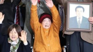 Kim Seong-ju (tengah) di antara para korban dan keluarga yang merayakan kemenangan mereka di Seoul.