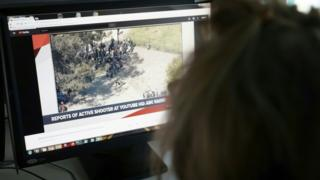 Journalist looking at a computer screen of Youtube shooting report