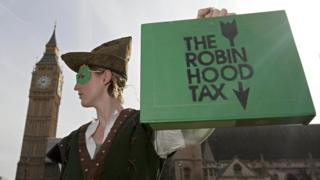 Campaigner for so-called Robin Hood tax, dressed as Robin Hood, stands outside parliament, 2010