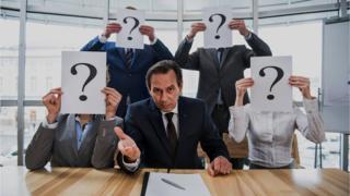 Personas tras un escritorio, con los rostros cubiertos con papeles con signos de interrogación