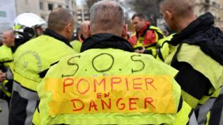"A firefighter with a vest reading ""SOS firefighters in danger"" takes part in a demonstration to protest against the pension overhauls, in Marseille, southern France, on 5 December, 2019"