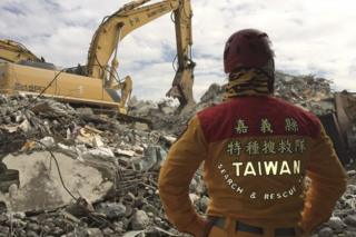 A rescue worker watches a digger at the collapsed building in Tainan, Taiwan (11 Feb 2016)
