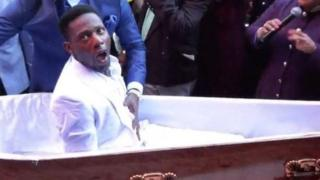 Pastor Alph Lukau stands next to the coffin and places his hand on the stomach of the man he is claiming to resurrect.