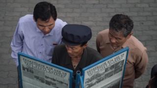 North Korean men read a newspaper in the street in Pyongyang (file image)