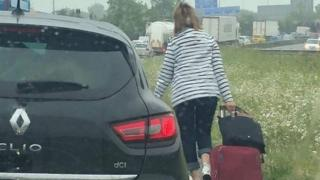 woman walks along road with luggage