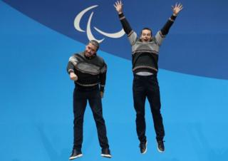 Alpine Skiing Men's Super Combined gold medallist Miroslav Haraus of Slovakia and his guide Maros Hudik jump in the air