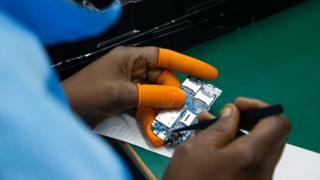 A Ugandan factory worker assembles a mobile phone mother board on December 02, 2019 in Namanve, Uganda.