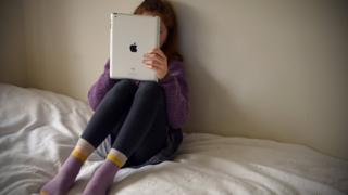 Child alone in bedroom on iPad