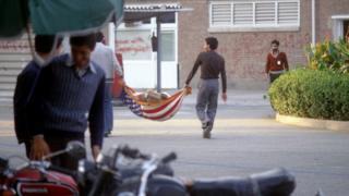 """دانشجویان وابسته به جریان موسوم به """"پیرو خط امام"""" در روز ۱۵ نوامبر ۱۹۷۹ با پرچم ایالات متحده آمریکا زباله جا به جا میکنند."""
