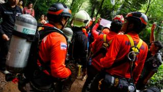 Rescue personnel carrying diving tanks on their backs gather at the cave site