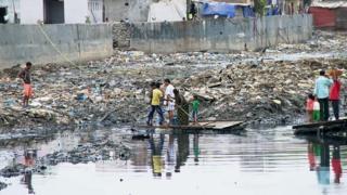 Жителям трущоб Мумбаи приходится пересекать канаву на плоту.