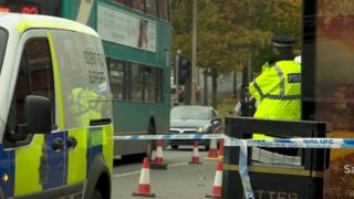 Police at scene of charity shop murder