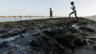 Foco em óleo vazado sobre areia, com banhistas no plano de fundo