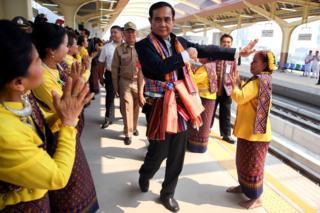 Le Premier ministre thaïlandais Prayuth Chan-ocha exécute une danse traditionnelle avec des artistes à la gare de Khon Kaen