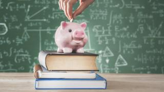 A stock image - showing a blackboard with lots of equations in the background. In the foreground a female hand puts a coin into a piggy bank that is standing on top of a pile of three books.