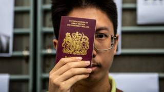 A Petitioner is seen holding up a BNO passport outside the British Consulate in Hong Kong on August 21, 2019