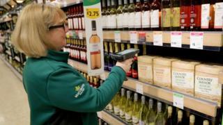 A member of staff scans groceries inside a Morrisons supermarket