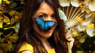 A Blue Morpho butterfly sits on the face of model Jessie Baker