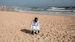 A member of the Layene community prays on the beach in front of the Yoff Layene Mosque, during the Islamic festivity of Korite in Dakar, Senegal, on May 24, 2020,