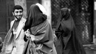 A mullah in a white turban, holding his little daughter in black chador in his arms, talks to a man, while accompanied by his wife, also in black chador with a net mask covering her face, as they head towards Friday prayers at Tehran university, 1 February 1980