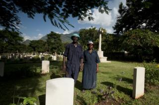 Shadrack Paull and Lusia Axalte stand holding hands among the graves at the cemetery in Tanzania