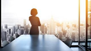 Mujer en una oficina con vistas a una ciudad.