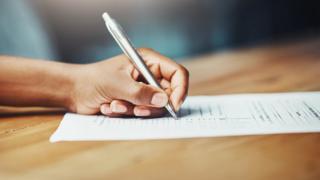 Mão segura caneta, que escreve em folha de papel sobre mesa