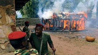 Soldiers run from a house set afire by protestors opposed to the Burundian president's bid to stand for a third term in Butagazwa, Mugongomanga, some 30km east of Bujumbura, on June 5, 2015