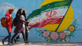 Young girls walk in front of a mural showing the Iranian national flag in the centre of the capital Tehran, on 23 April