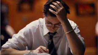 Joven se toma la cabeza mientras resuelve un examen
