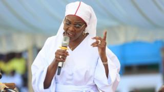 Grace Mugabe, with a microphone speaking, dressed all in white in November image