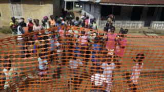 People wait to be released from Ebola quarantine in the village of Massessehbeh on the outskirts of Freetown, Sierra Leone on Aug. 14, 2015,
