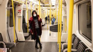 A woman wears a protective mask as she travels on an underground train in London