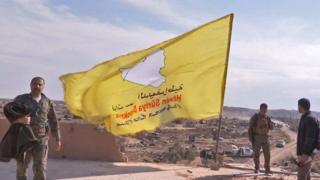 Miembros de las Fuerzas Democráticas Sirias colocando una bandera