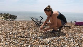 Kiko Matthews picking up litter on a beach