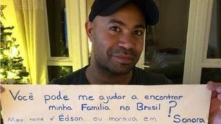 Edson segurando cartaz com informações sobre seus pais e sua adoção