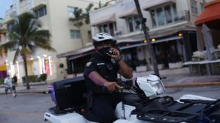 sports A Miami police officer wears a mask to enforce the city's mask mandate