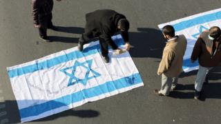 Iranian protesters pour kerosene on an Israeli flag during the funeral procession of Brigadier General Mohammad Ali Allahdadi in Tehran on January 21, 2015.