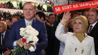Cumhurbaşkanı Recep Tayyip Erdoğan ile eşi Emine Erdoğan kongre salonuna gelen kalabalığı selamlıyor. Cumhurbaşkanı Erdoğan elindeki karanfilleri dağıtıyor.