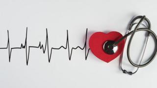 Estetoscópio, a figura de um coração e um eletrocardiograma ilustrado