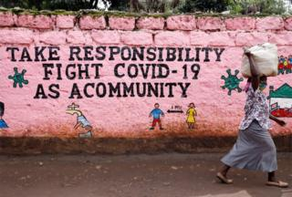 A woman walks past a mural whose slogan reads: