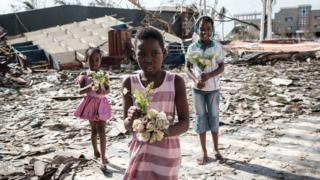 Girls collect artificial flowers from the rubble of a building destroyed by the cyclone Idai at Sacred Heart Catholic Church in Beira, Mozambique, on March 24, 2019.
