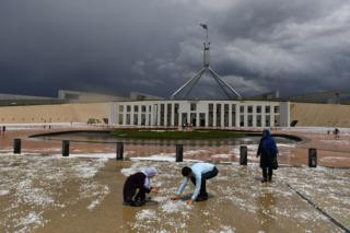 People look at hail stones on the ground after a severe hail storm at Parliament House