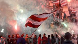 Tunisian Club Africain's supporters wave flags and burn flares during a friendly with Paris Saint Germain on January 4, 2017, in Rades.