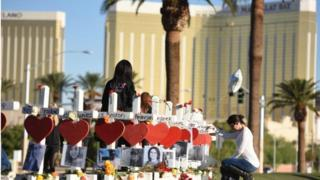 A woman prays near the 58 crosses for the victims of the Las Vegas shooting just south of the Mandalay Bay hotel.